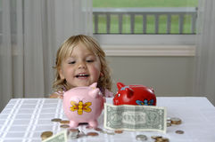 Preschool girl and piggy banks stock image
