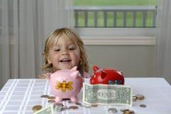 Preschool girl and piggy banks Stock Image