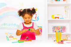 Preschool girl play with modeling clay in class. Beautiful Hispanic girl play with plasticine in the class at kindergarten royalty free stock image