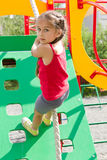 Preschool girl playing on playground, climbing the wall on a rope Royalty Free Stock Images