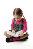 Preschool girl reading. Cute preschool girl with pigtails reading and pointing at a book Stock Image