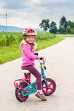 Preschool girl is sitting on bike. Preschool girl with helmet and pink hoodie is sitting on bike and looking at camera stock photos