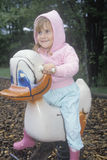 A preschool girl sitting on a duck ride Stock Images