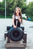 Preschool girl sitting on top of a cannon. Close view royalty free stock photography