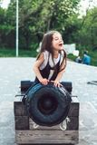 Preschool girl sitting on top of a cannon. Close view stock photo