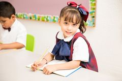 Preschool girl in uniform in a classroom. Portrait of a pretty girl attending preschool and wearing a uniform in a classroom stock photos
