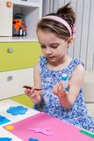A preschool girl use glue for homework Royalty Free Stock Images