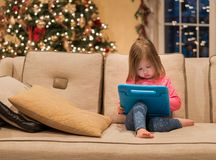 Preschool girl using a tablet computer at home at Christmas Royalty Free Stock Images