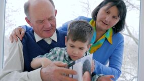 Preschool home education, grandparents with grandson read magazine. Indoors stock video footage