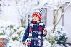 Funny little kid boy in colorful clothes playing outdoors during strong snowfall. Preschool kid boy in colorful clothes playing outdoors during strong snowfall Royalty Free Stock Image