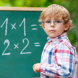Preschool kid boy with glasses at blackboard practicing mathemat Royalty Free Stock Photography