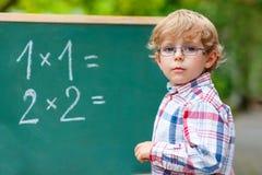 Preschool kid boy with glasses at blackboard practicing mathemat Stock Photos