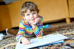 Preschool kid boy at home making homework, painting a story with colorful pens. Cute little preschool kid boy at home making homework, painting a story with stock image
