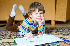 Preschool kid boy at home making homework, painting a story with colorful pens. Cute little preschool kid boy at home making homework, painting a story with stock photos