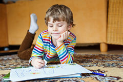 Preschool kid boy at home making homework, painting a story with colorful pens Stock Photo