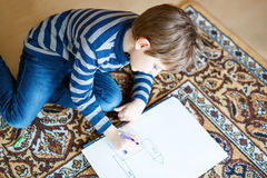 Preschool kid boy at home making homework, painting a story with colorful pens royalty free stock image