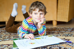 Preschool kid boy at home making homework, painting a story with colorful pens. Cute little preschool kid boy at home making homework, painting a story with royalty free stock photo