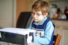 Preschool kid boy at home making homework, painting a story with colorful pens stock image