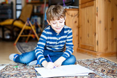 Preschool kid boy at home making homework, painting a story with colorful pens Royalty Free Stock Photos