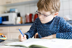 Preschool kid boy at home making homework writing letters with colorful pens. Cute little kid boy with glasses at home making homework, writing letters with stock photo