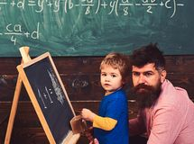 Preschool kid and his teacher in the classroom. Father helping his little boy with math. Daddy hugging his kid. Preschool kid and his teacher in the classroom royalty free stock images
