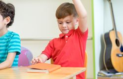 Preschool kid raise arm up to answer teacher question on whiteboard in classroom,Kindergarten education concept.  stock image