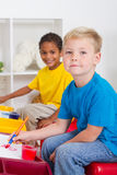 Preschool kids. Two happy preschool kids in class painting at their desks Royalty Free Stock Image