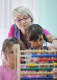 Preschool kids. Happy child kids group have fun and play at kindergarden indoor preschool education concept with teacher stock photography