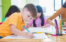 Preschool kids drawing with color pencil on white paper on table. In classroom with friends and teacher,Kindergarten education concept royalty free stock images