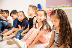 Preschool kids sitting on the classroom floor. Portriat of a beautiful Hispanic little girl sitting on the floor for class and smiling royalty free stock image