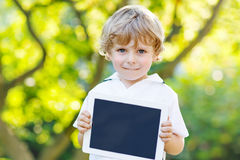 Preschool little boy with tablet pc, outdoors Royalty Free Stock Images