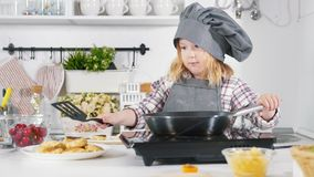 Preschool little girl baker making cheesecakes cookies on metal pan. Close up stock footage