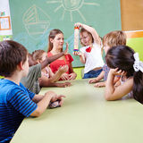 Preschool musical education. With group of children and rainmaker Stock Photos