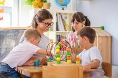 Preschool nauczyciel z dziećmi bawić się z kolorowymi dydaktycznymi zabawkami przy dziecinem fotografia royalty free