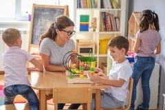 Preschool nauczyciel z dziećmi bawić się z kolorowymi dydaktycznymi zabawkami przy dziecinem fotografia stock