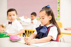 Preschool pupils writing in a classroom. Cute preschool students wearing a uniform and doing a writing assigment in a classroom royalty free stock image