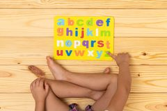 Kid Learning the Alphabet. Preschool student learning the alphabet letters playing on the floor at home royalty free stock photos