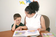 Preschool student and teacher reading a book Stock Photography