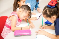 Preschool students during class. Group of preschool students working on a writing assignment in a classroom stock image