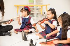 Preschool students learning some music. Pretty Latin girls in a preschool class learning some music with their teacher stock photography