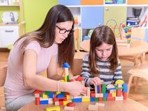 Preschool Teacher and Child Concentrated on on Bulilding Toy Castle Royalty Free Stock Images