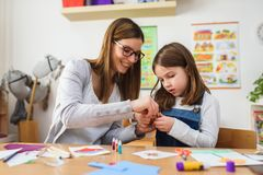 Preschool teacher with child at Kindergarten - Creative Art Class. Kindergarten teacher helping a child. Mother with her daughter having creative and fun time stock photography