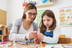 Preschool teacher with child at Kindergarten - Creative Art Class. Kindergarten teacher helping a child. Mother with her daughter having creative and fun time stock images