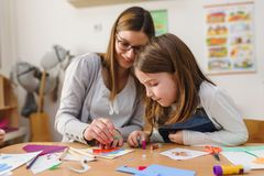 Preschool teacher with child at Kindergarten - Creative Art Class. Kindergarten teacher helping a child. Mother with her daughter having creative and fun time royalty free stock image