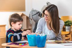 Preschool teacher with child at Kindergarten - Creative Art Class. Kindergarten teacher helping a child. Mother with her son having creative and fun time stock images
