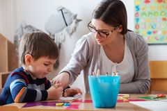 Preschool teacher with child at Kindergarten - Creative Art Class. Kindergarten teacher helping a child. Mother with her son having creative and fun time stock photos