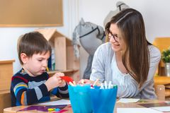 Preschool teacher with child at Kindergarten - Creative Art Class. Kindergarten teacher helping a child. Mother with her son having creative and fun time stock image