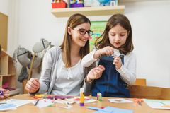 Preschool Teacher with Child at Kindergarten - Creative Art Class. Kindergarten teacher helping kids. Mother with child having creative and fun time stock image