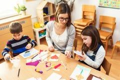Preschool Teacher with Children at Kindergarten - Creative Art Class. Kindergarten teacher helping kids. Mother with her children having creative and fun time stock photos