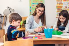 Preschool Teacher with Children at Kindergarten - Creative Art Class. Kindergarten teacher helping kids. Mother with her children having creative and fun time royalty free stock photography